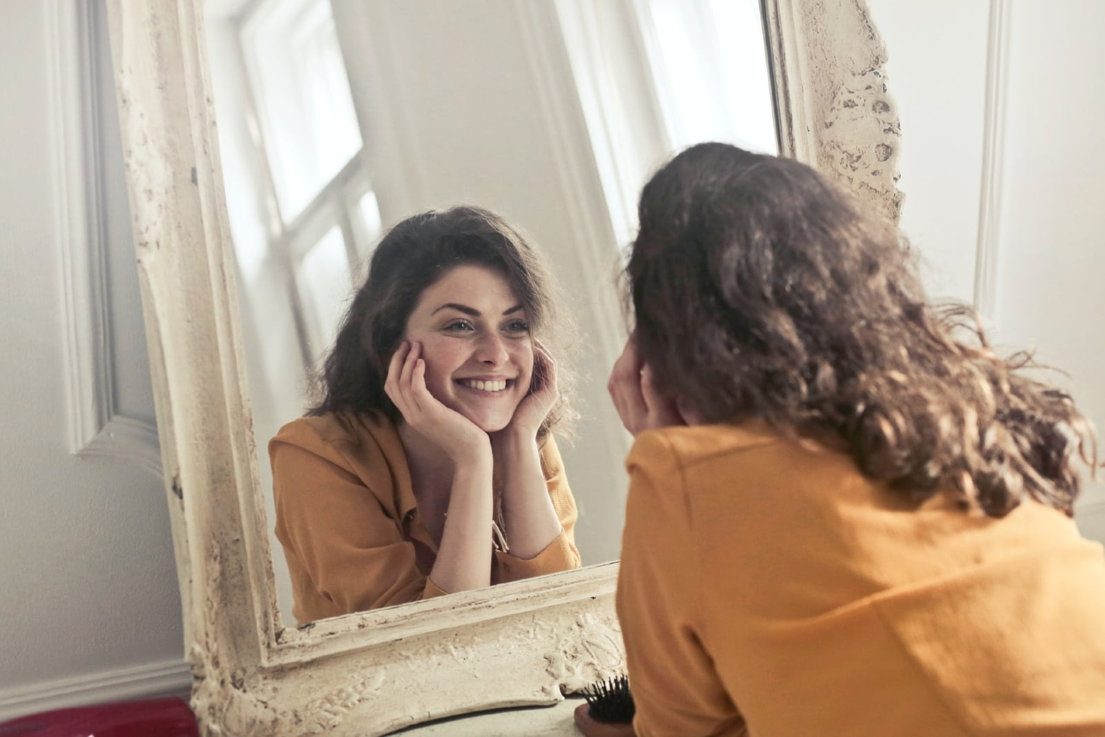 happy woman in yellow blouse looking in the mirror
