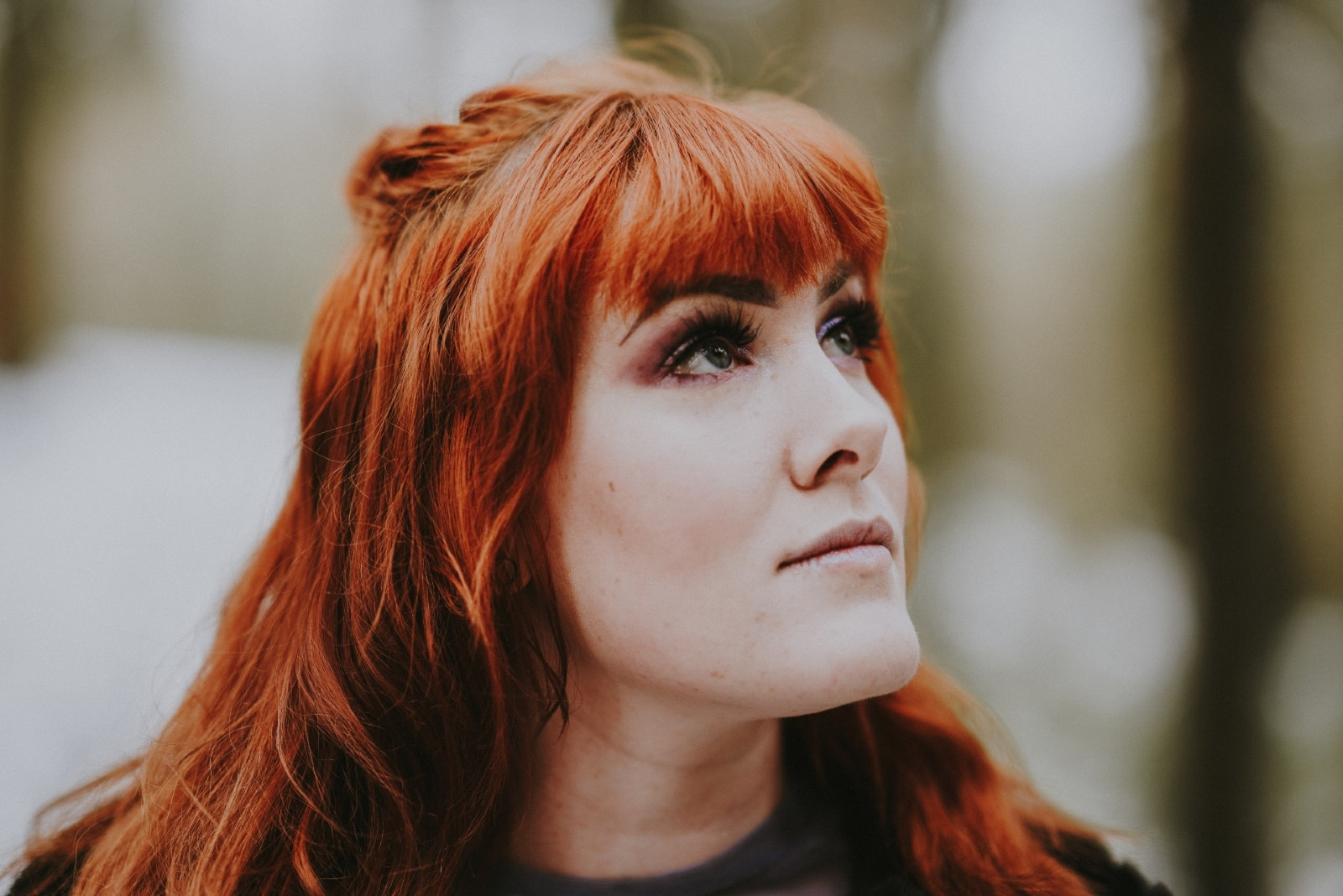 red haired woman looking up while standing outdoor
