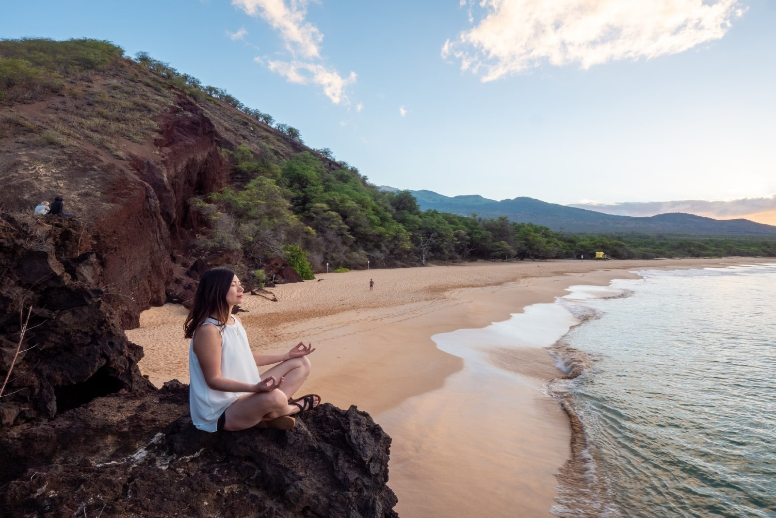 woman meditating while sitting on rock