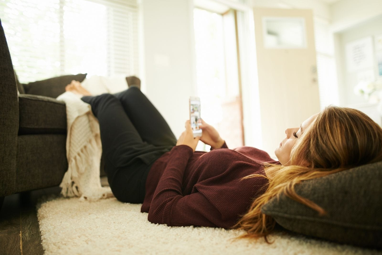 woman relaxing at home lying down and checking her phone