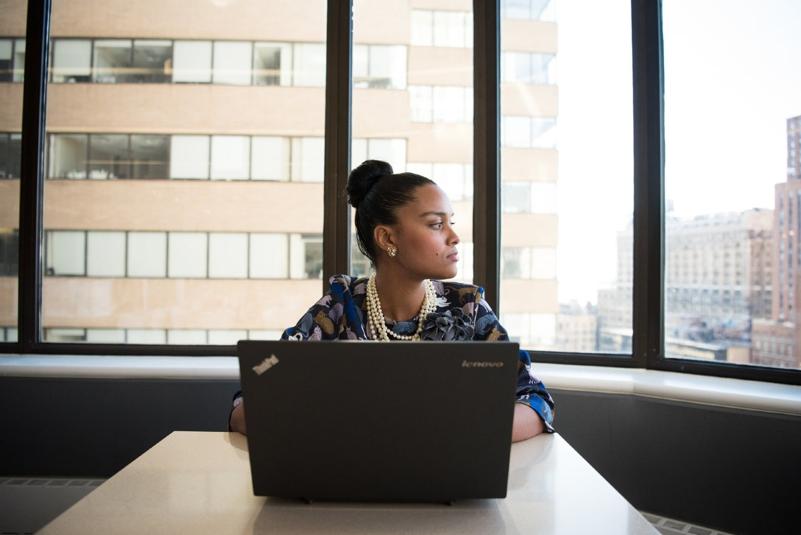 woman sitting in front of black laptop in office