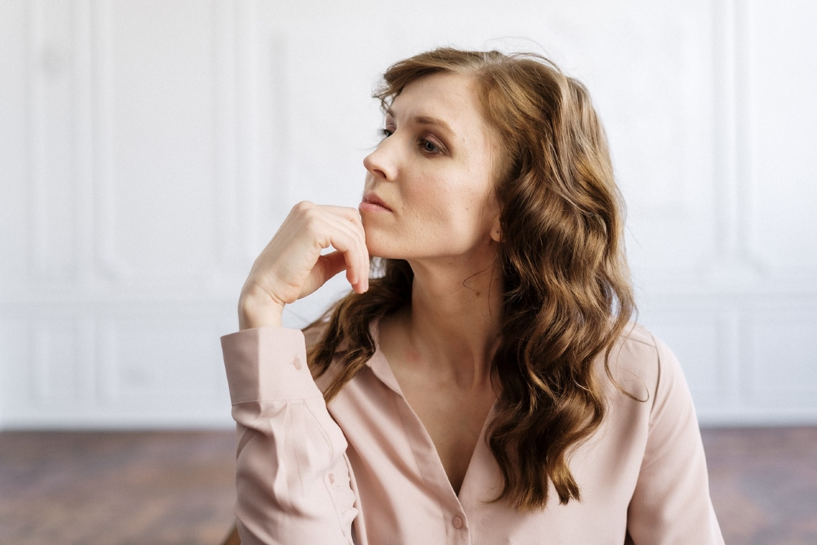 pensive woman in white shirt sitting indoor