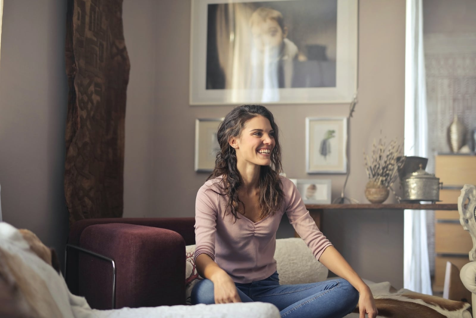woman in pink shirt smiling while sitting indoor