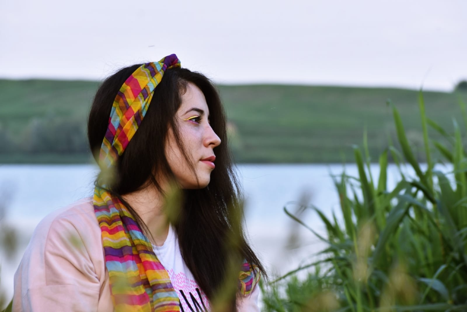 woman with colorful head scarf sitting near water