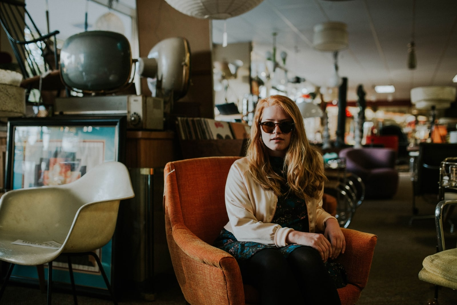 woman with sunglasses sitting on orange armchair