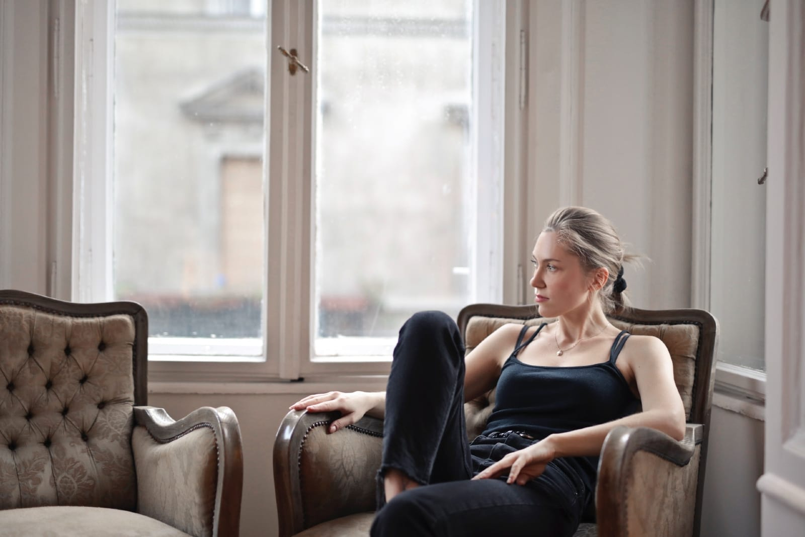 woman in black top sitting on armchair near window