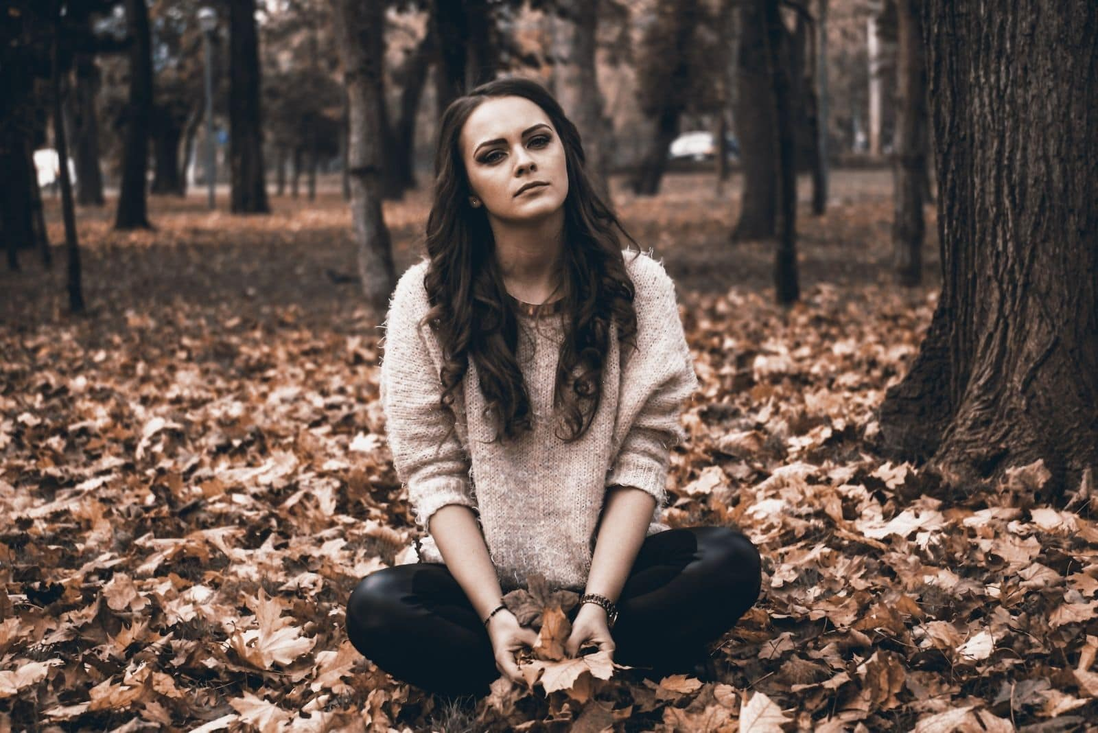 woman sitting on autumn folliage looking sad and alone