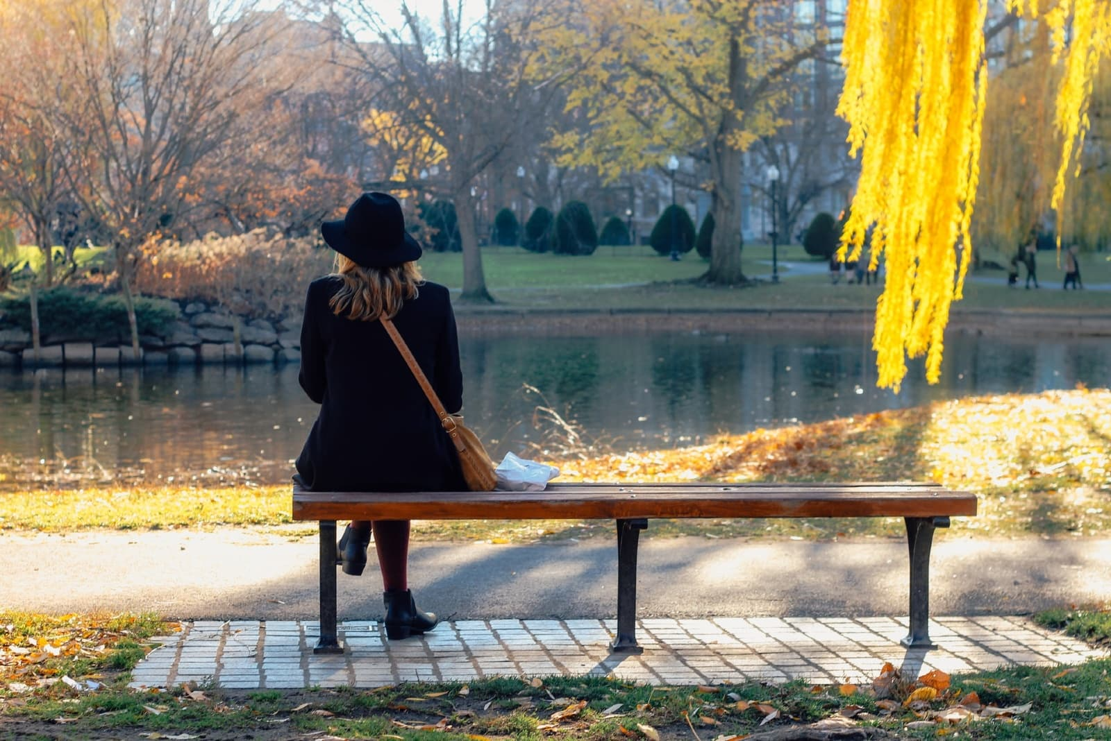 woman with black hat sitting on bench looking at water