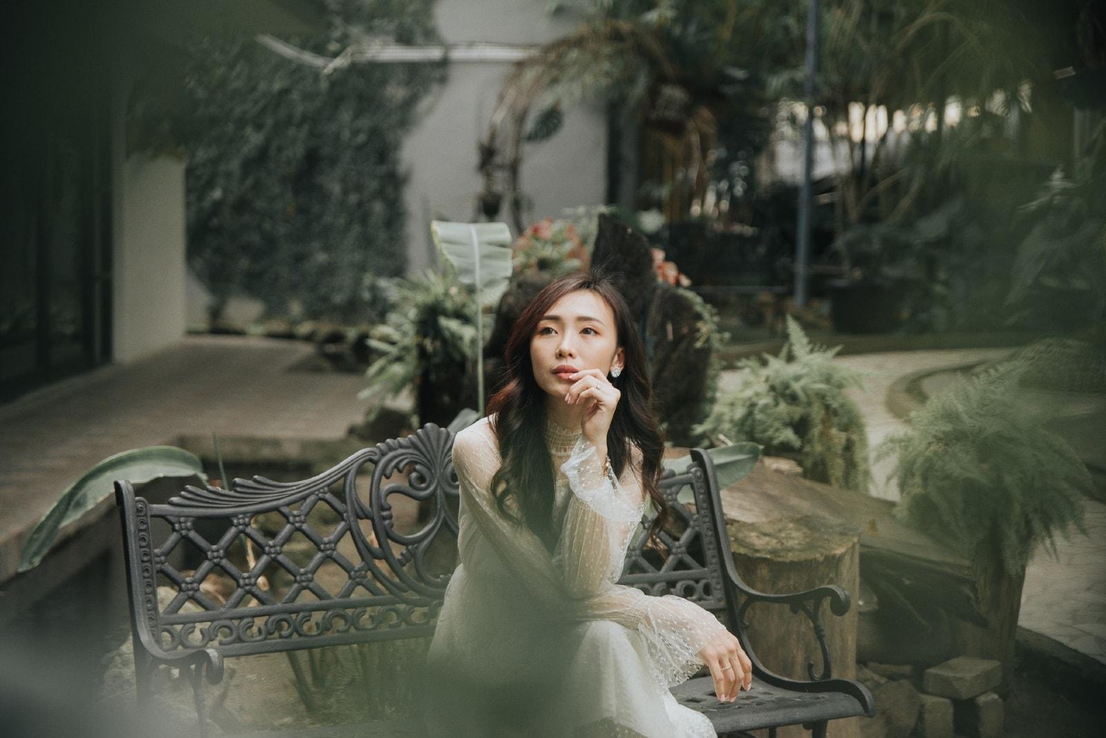 woman in white dress sitting on black metal bench