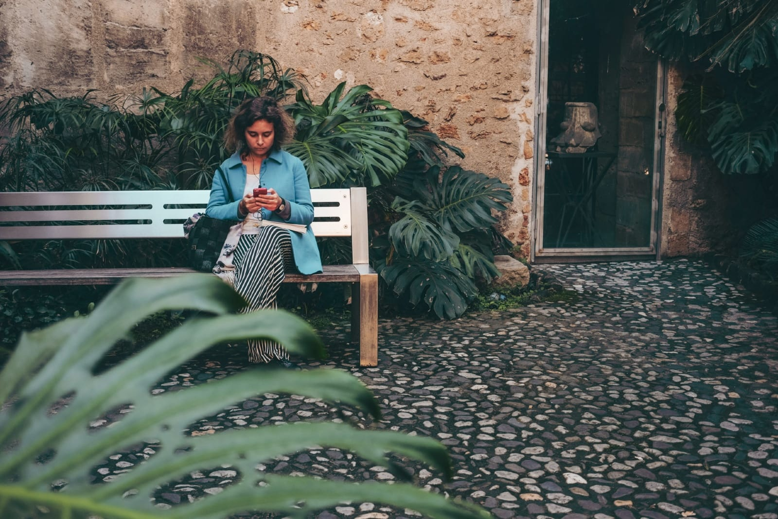 woman using smartphone while sitting on bench