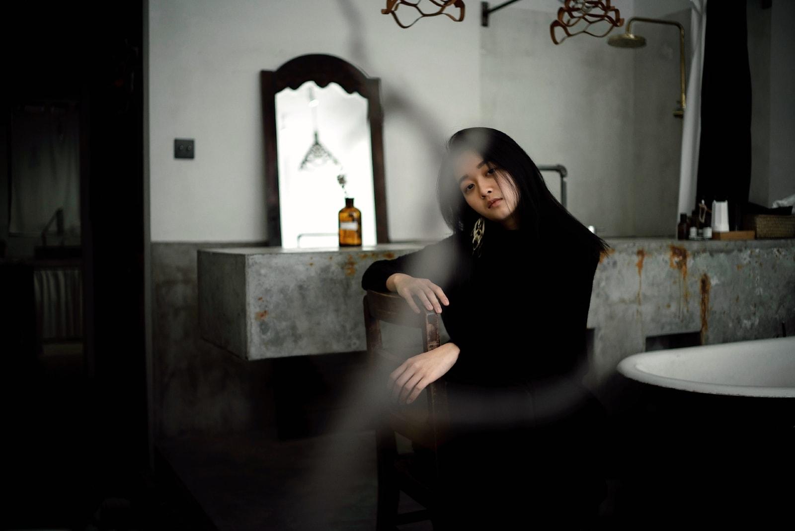 sad woman sitting on chair near mirror