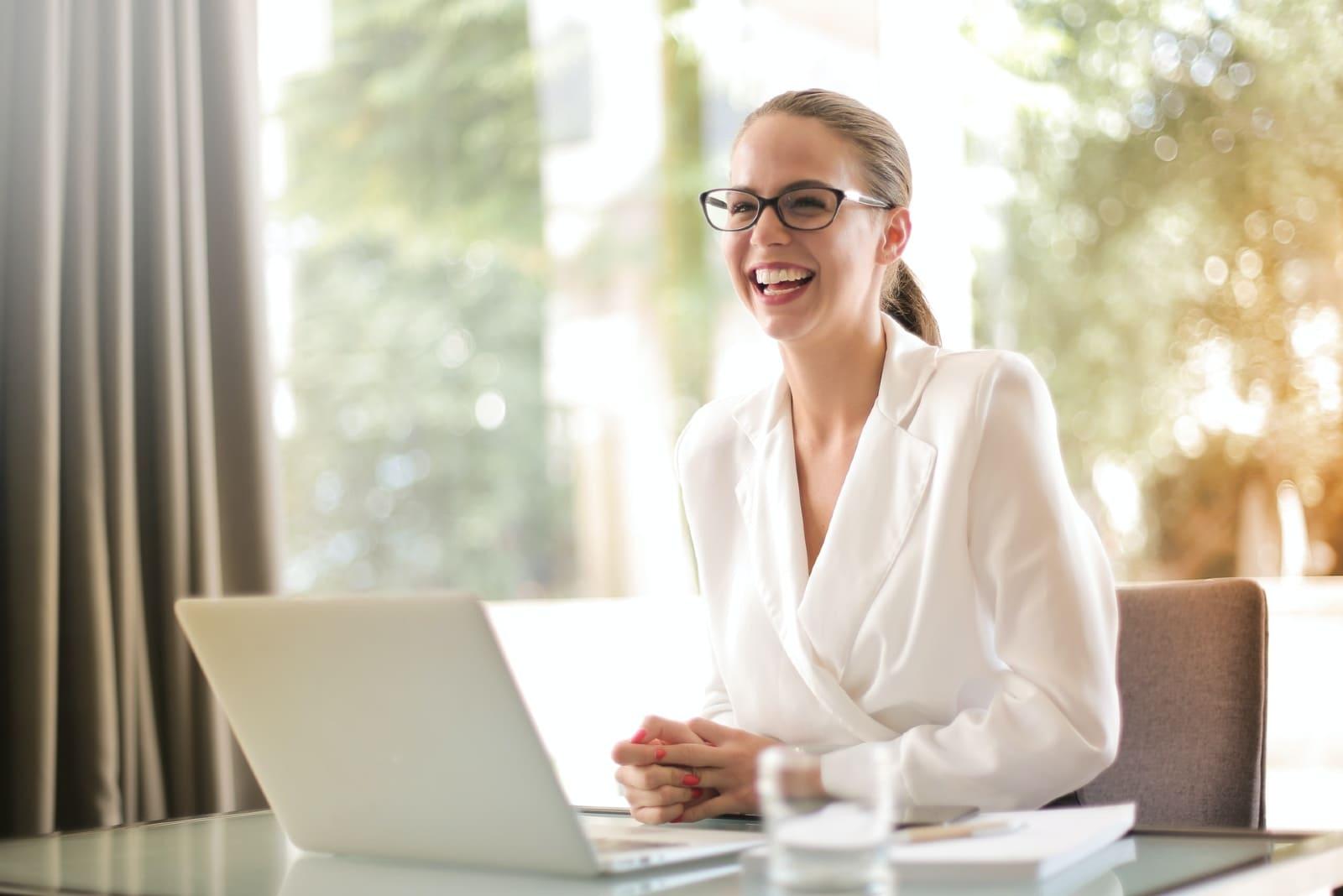 happy woman with eyeglasses sitting on chiar