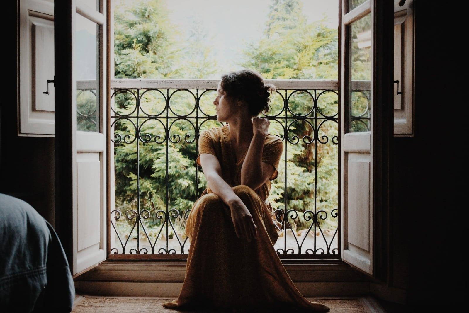 woman in long dress sitting on floor near window