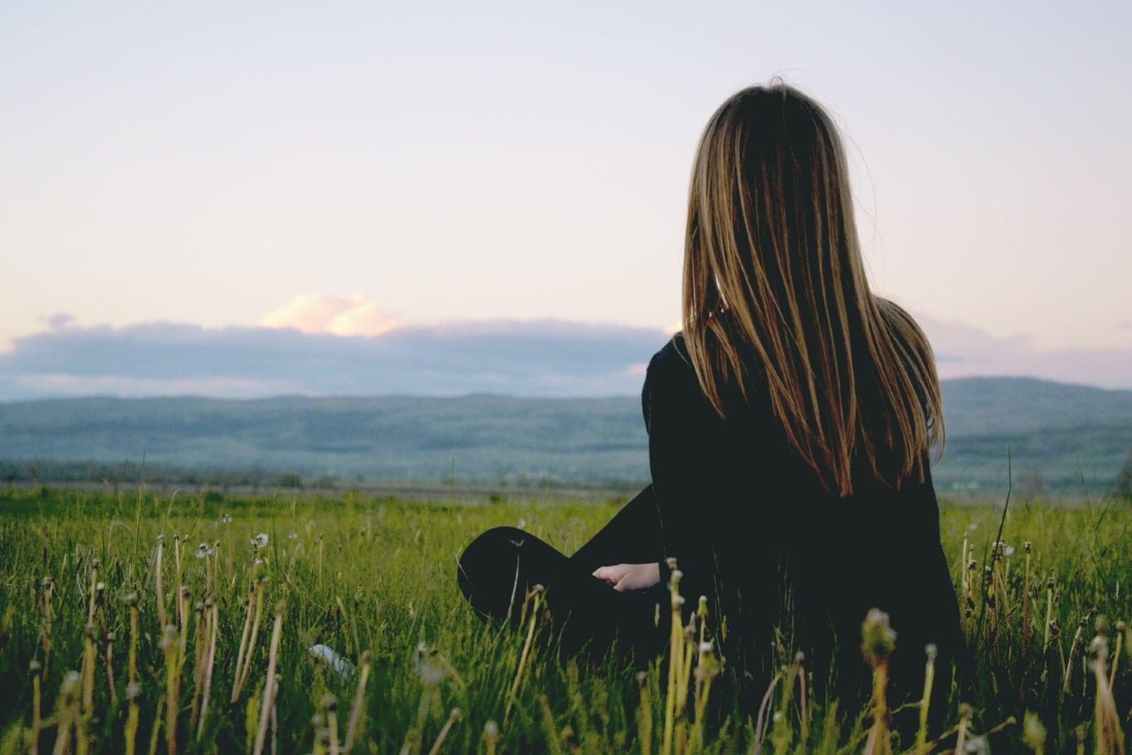 woman in black shirt sitting on grass