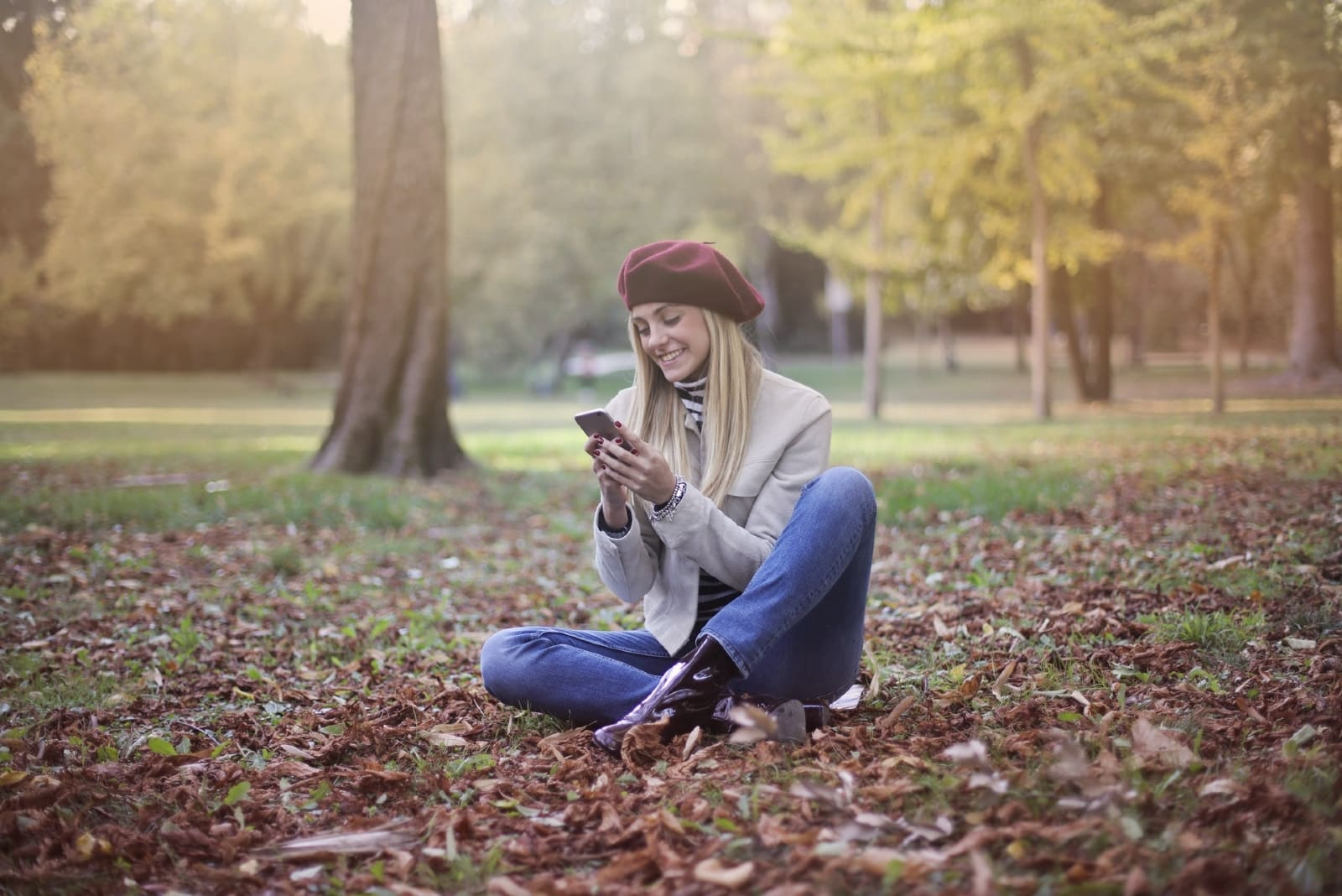 woman looking at phone while sitting on ground