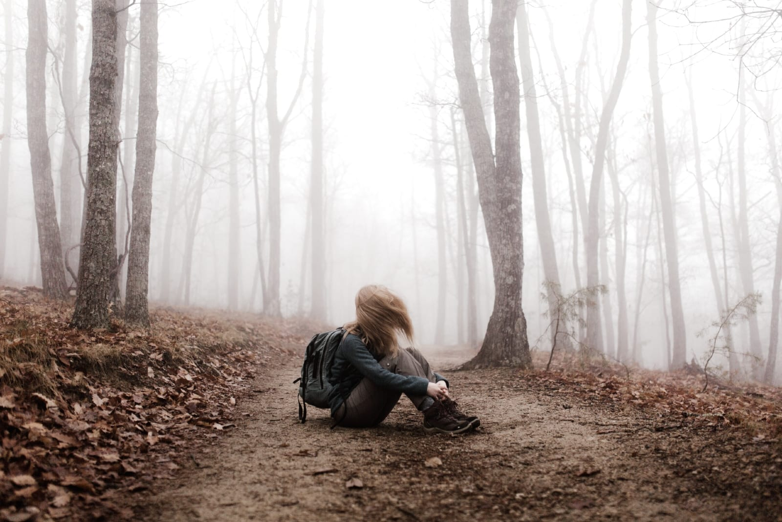 woman sitting on ground in forest