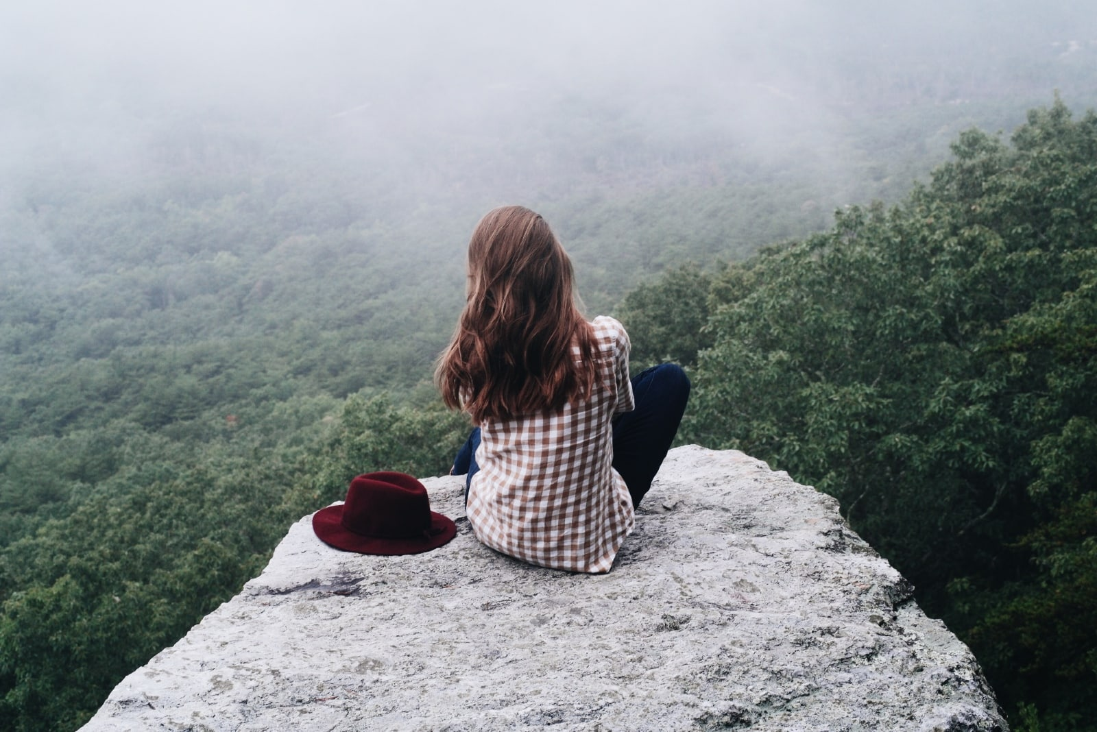 woman sitting on rock near red hat