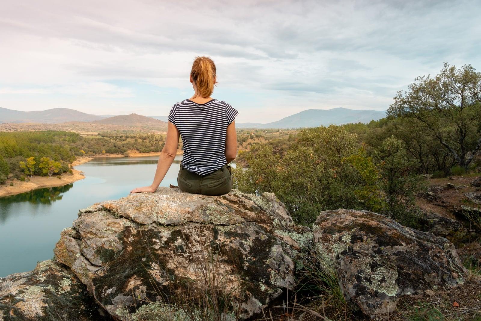 woman sitting on rock looking at lake