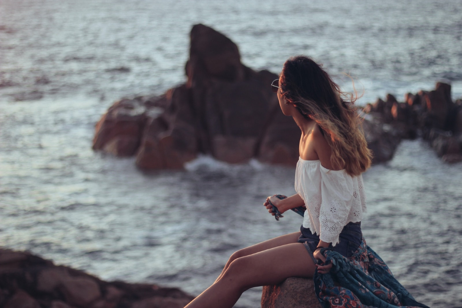 woman in white top sitting on rock looking at sea