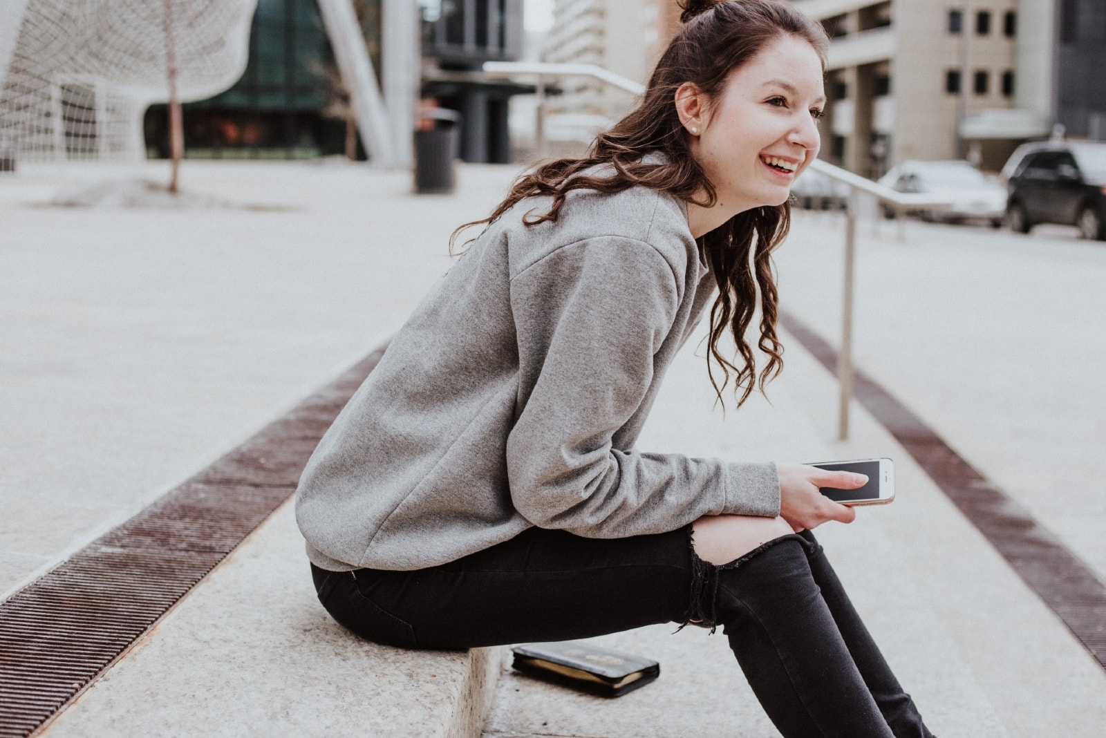 woman in gray sweatshirt sitting on stairs smiling