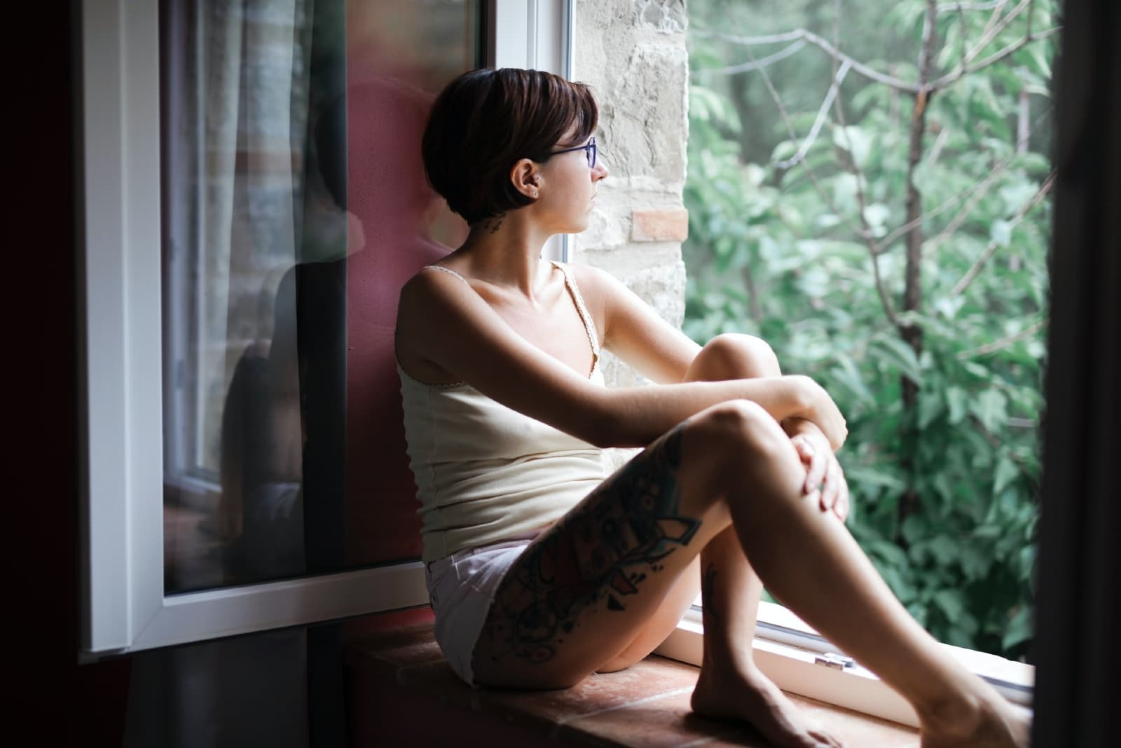 woman in white top sitting on window pane looking outside