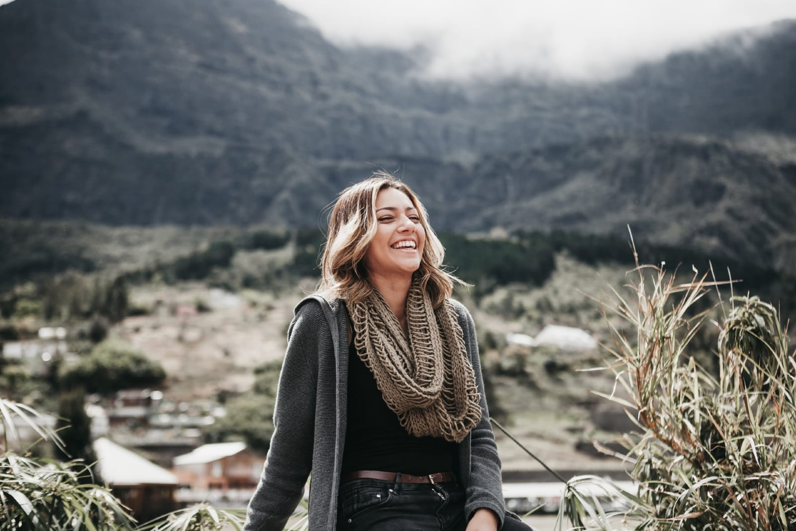 woman with gray scarf sitting outdoor smiling