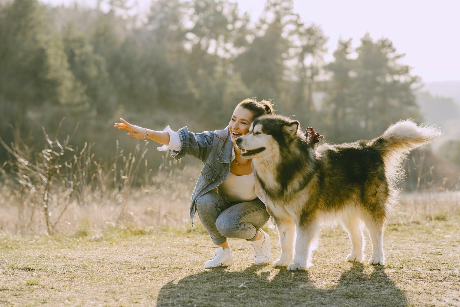 woman in denim jacket smiling near dog