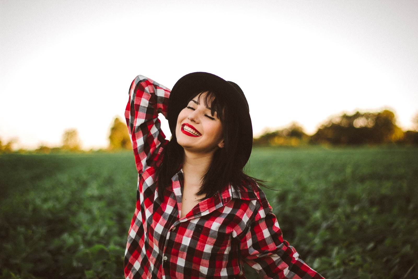 woman with black hat smiling while standing in the field