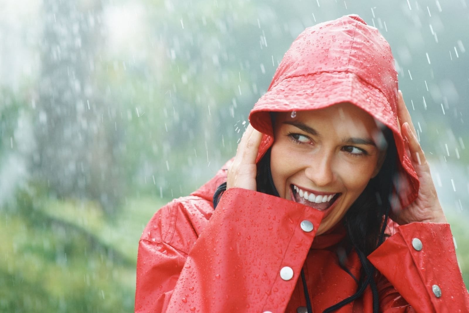 woman smiling white out in the rain wearing raincoat