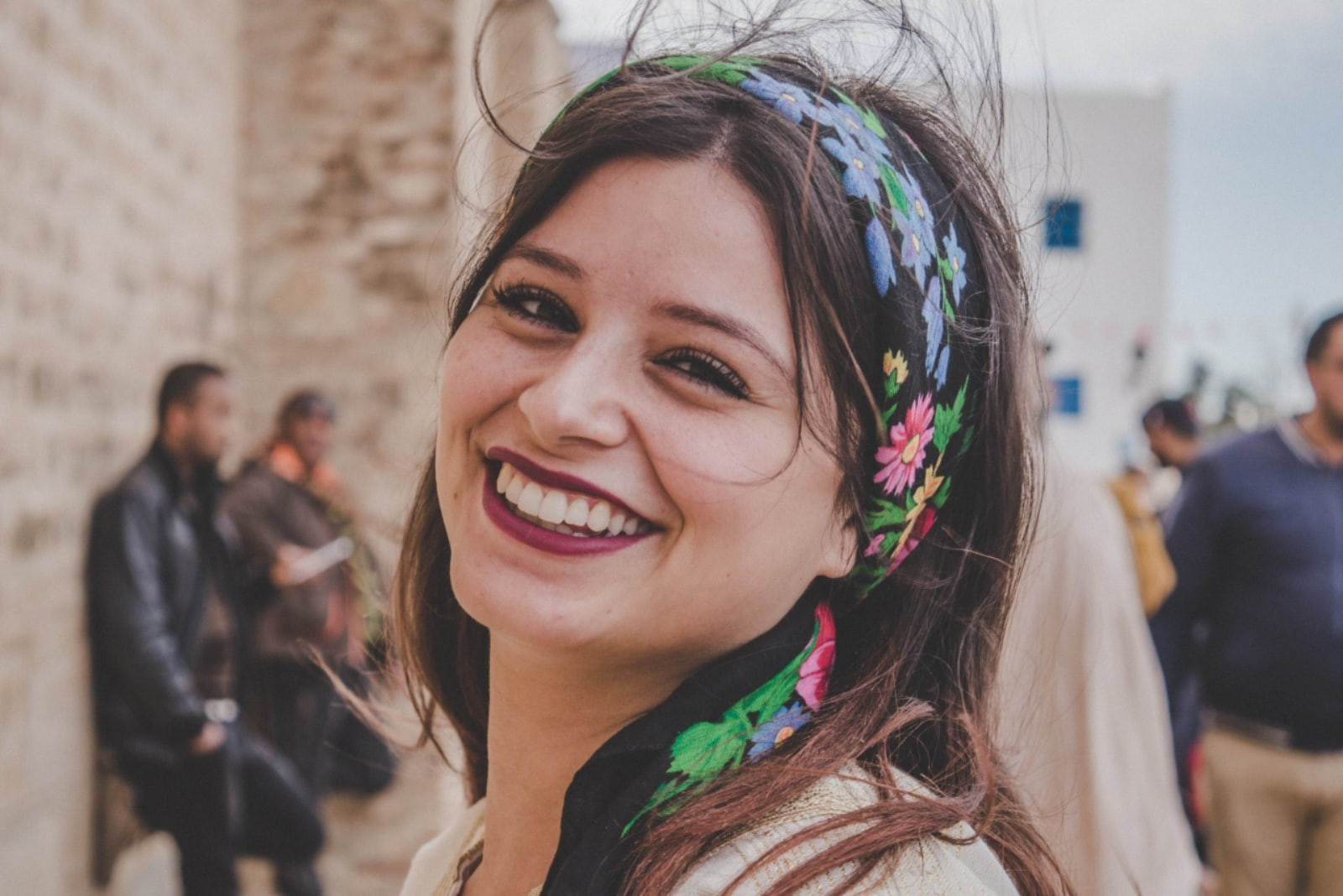 woman with colorful head scarf smiling