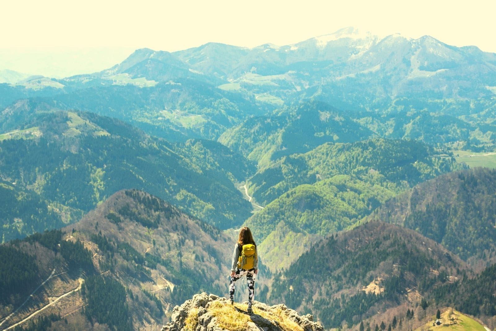 woman standing at the mountain top looking over the mountain ranges in very distant view