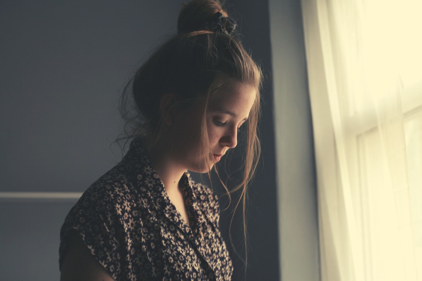 woman standing near the white window curtain sad and pensive