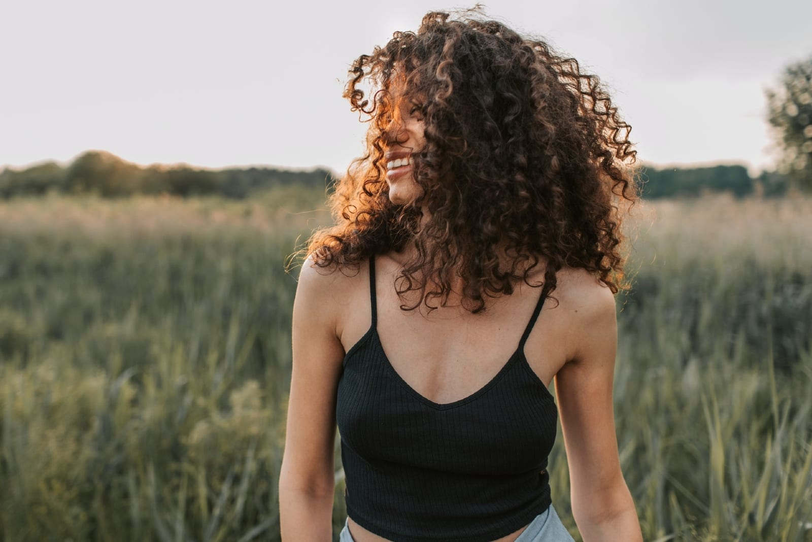 woman with curly hair standing in the field smiling