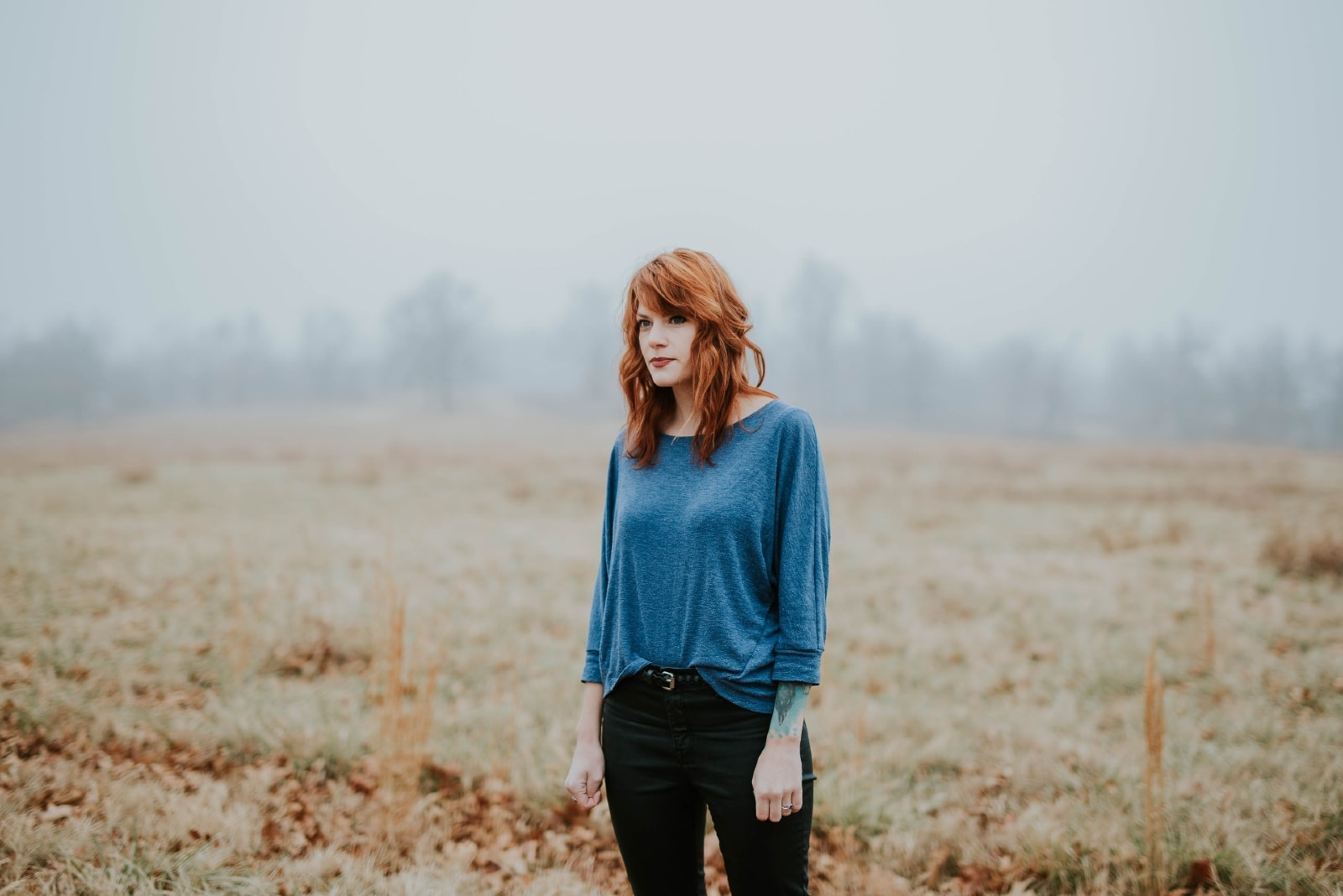 woman in blue top standing in the field