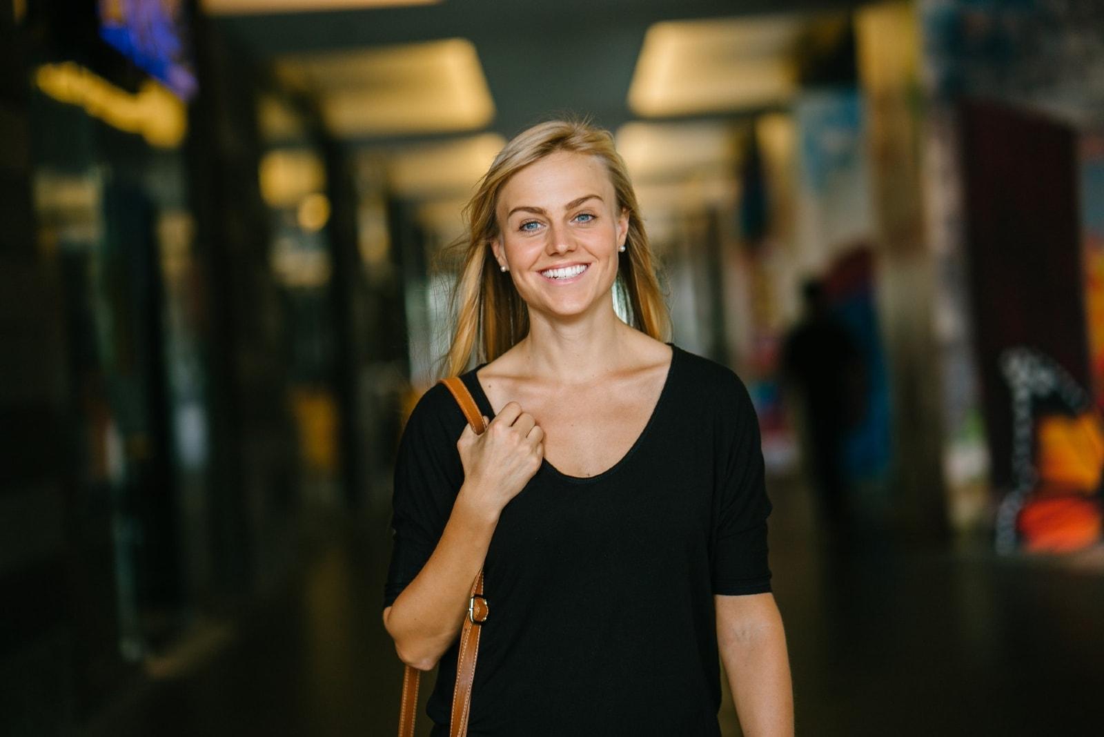 happy woman in black top standing indoor