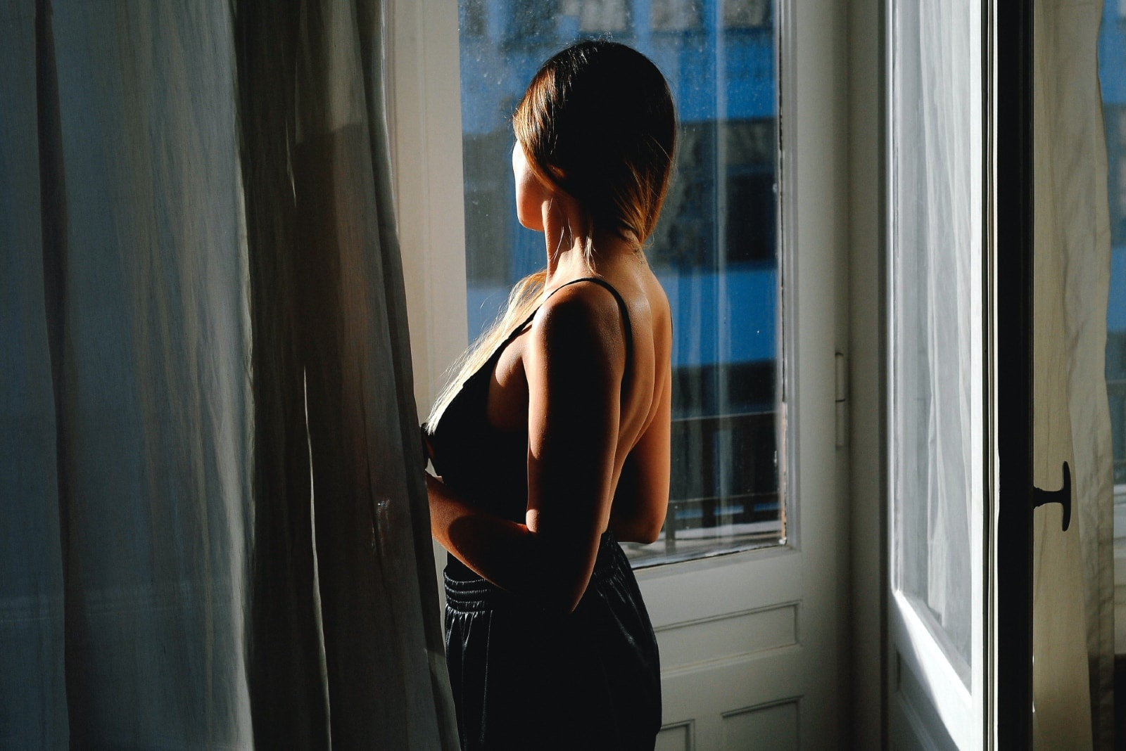 woman in black top standing near door looking outside