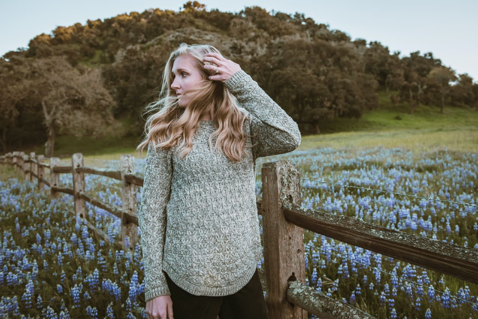 woman in gray sweater standing near wooden fence