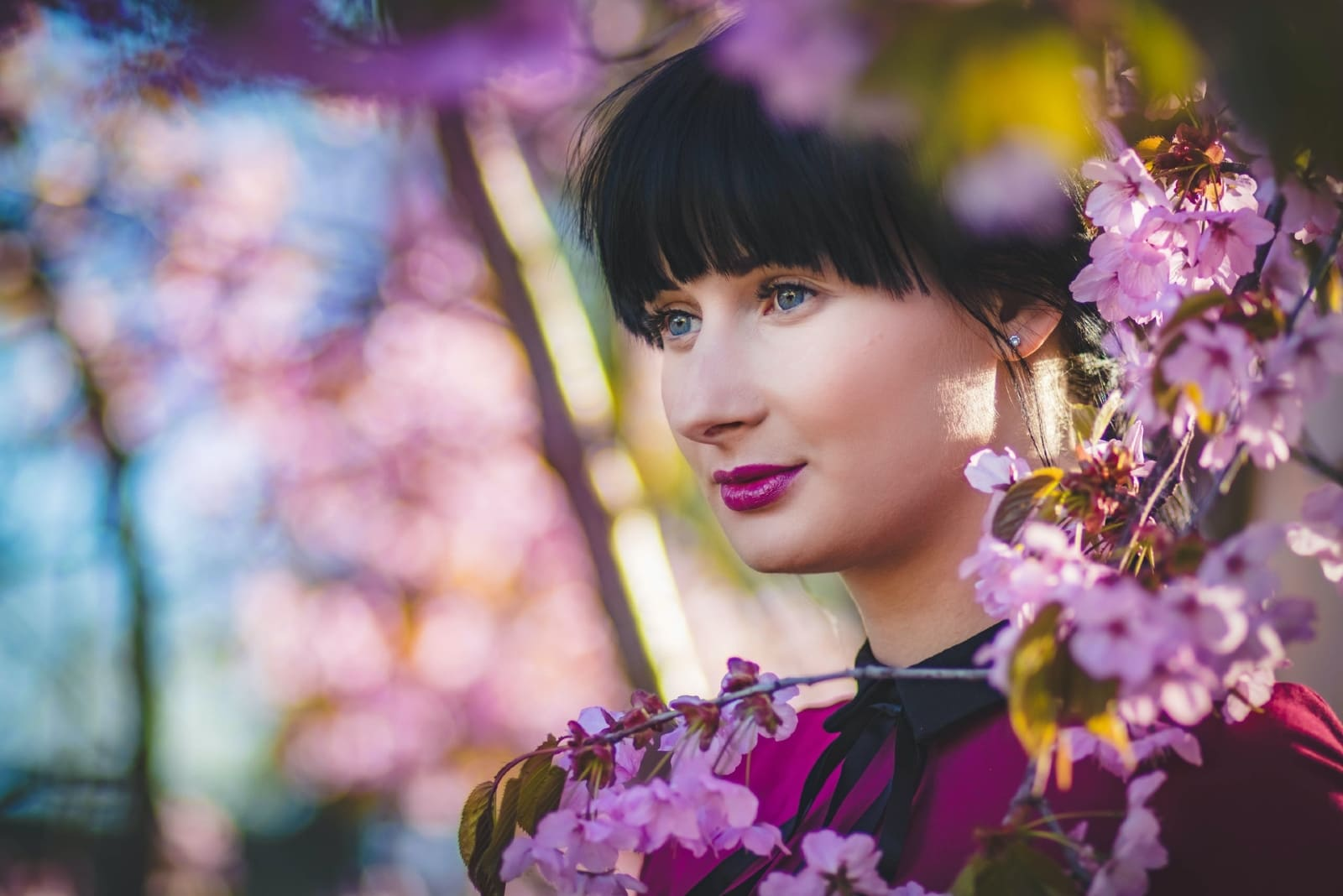 woman with purple lipstick standing near pink flowers