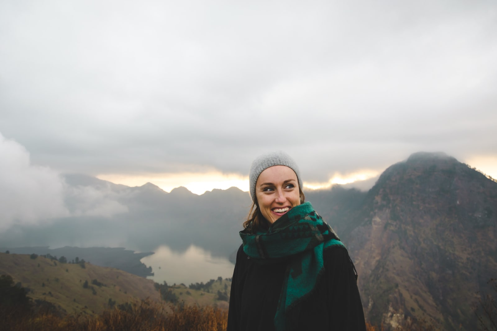 woman with green scarf smiling while standing near mountain
