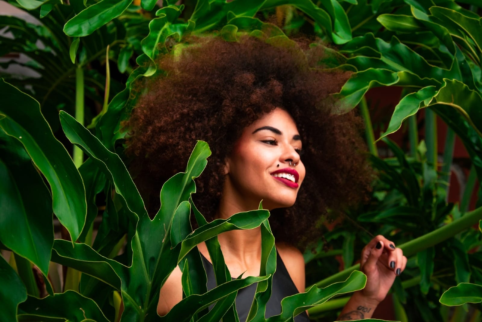 happy woman with curly hair standing near plant