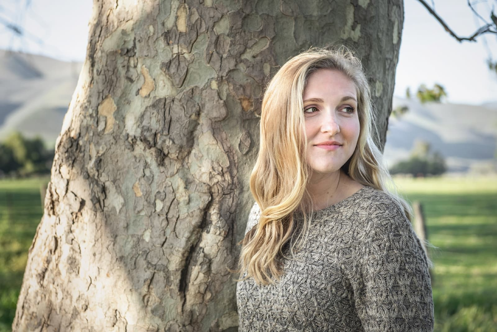 blonde woman in gray sweater standing near tree