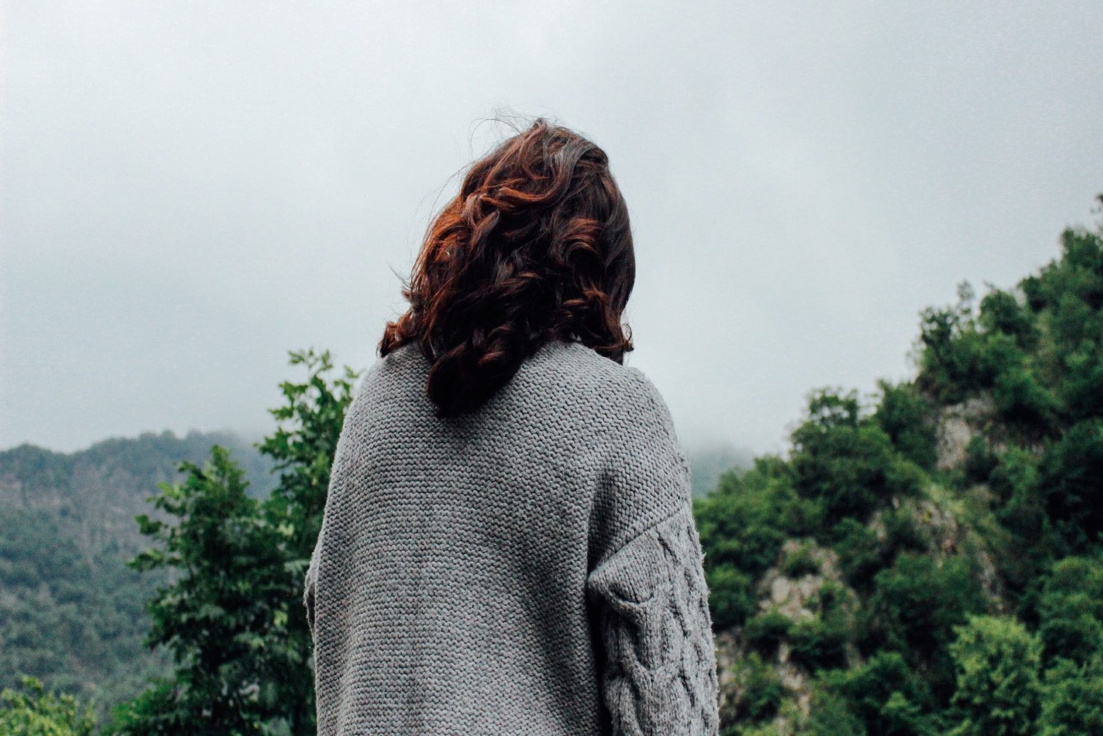 woman in gray sweater standing near tree