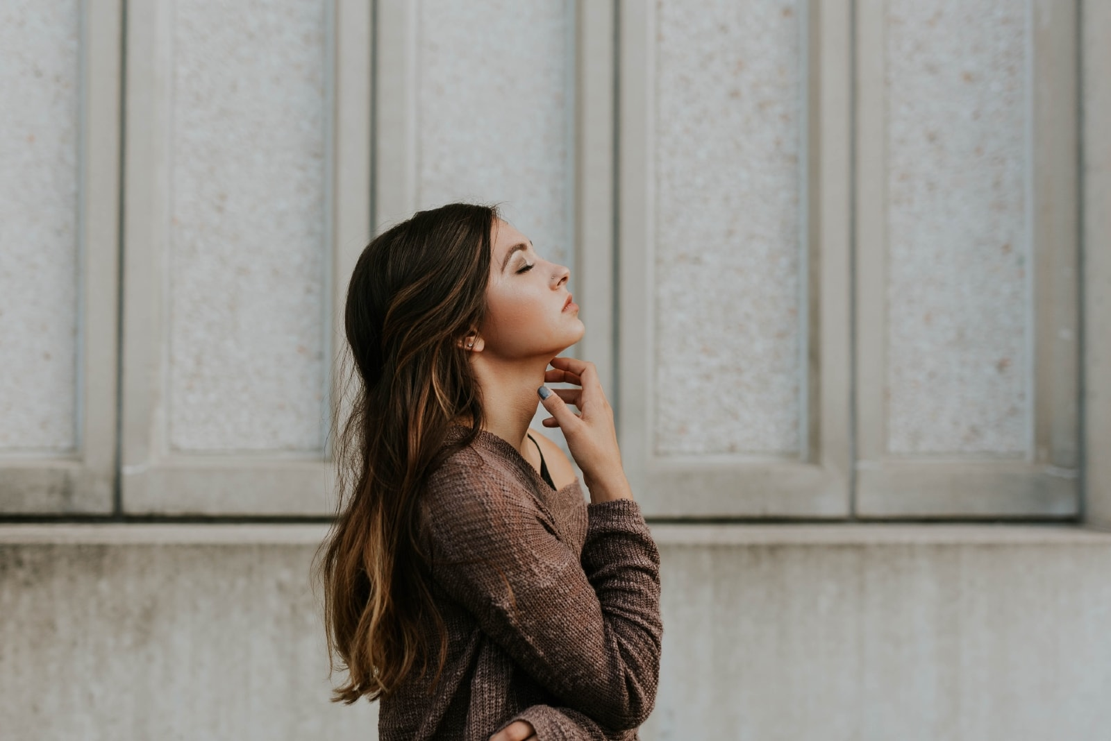 woman with eyes closed standing near wall
