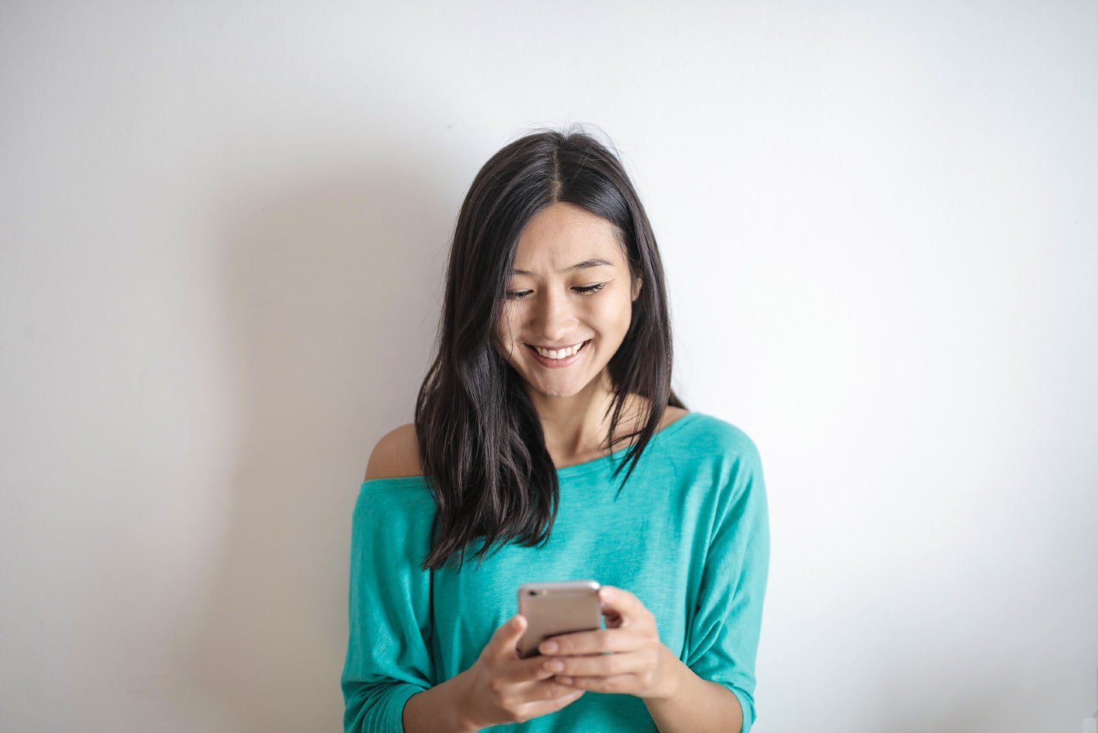 happy woman using smartphone while standing near wall