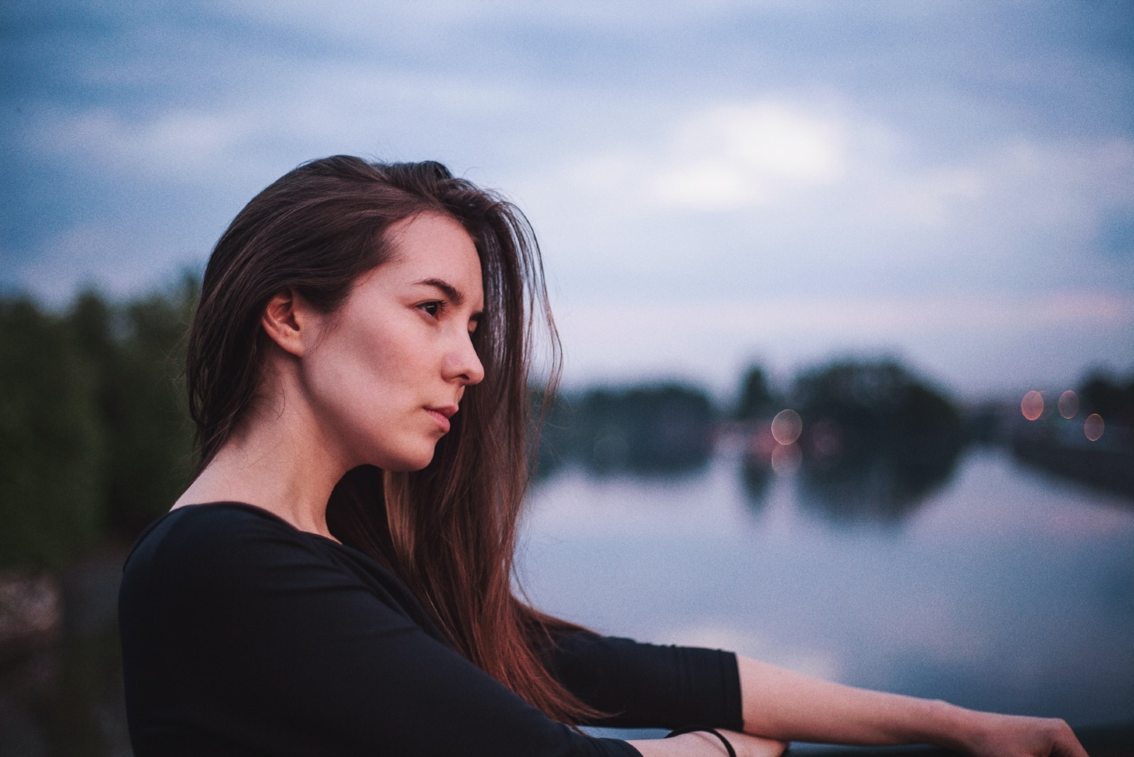 pensive woman in black top standing near water