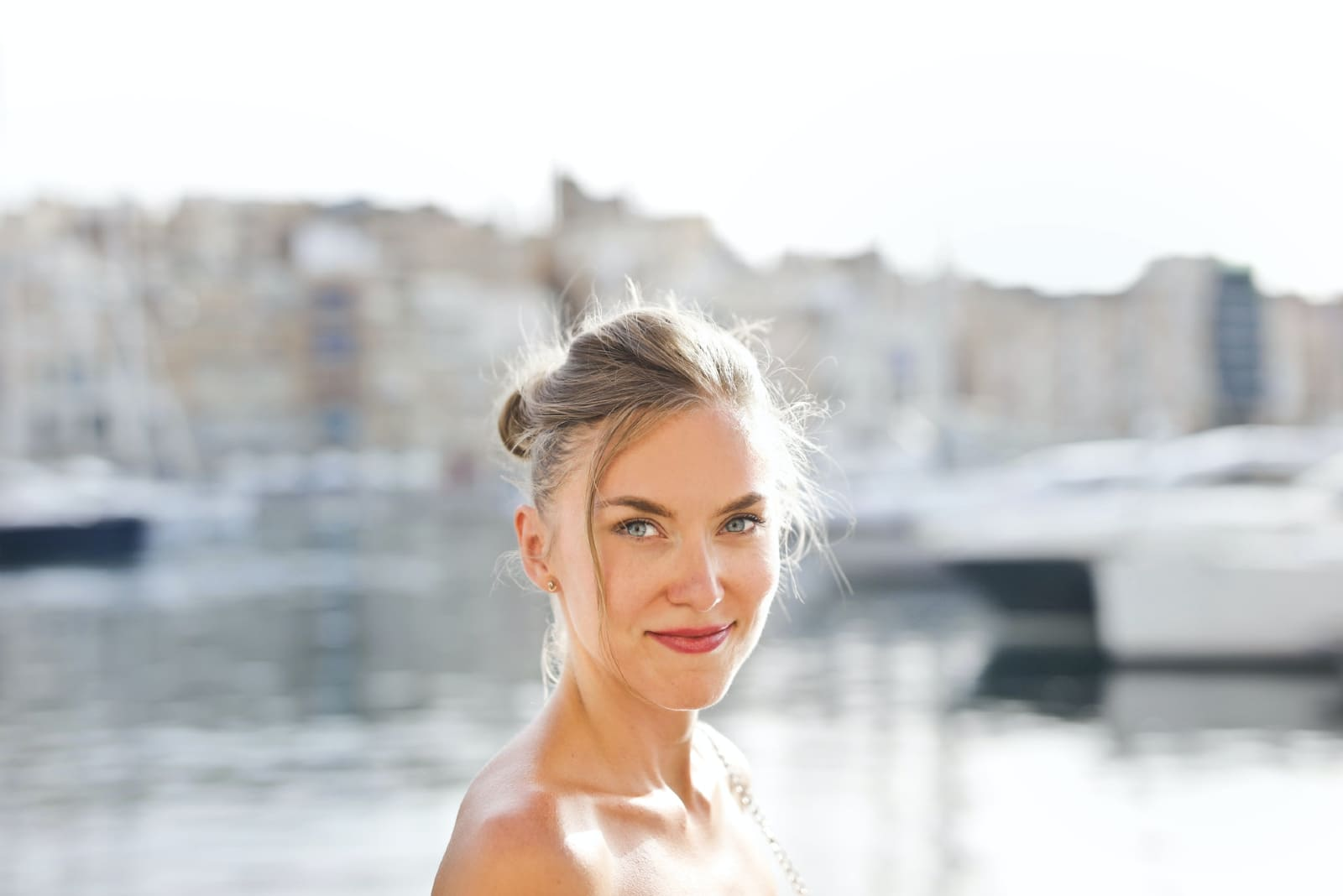 happy woman with green eyes standing near water