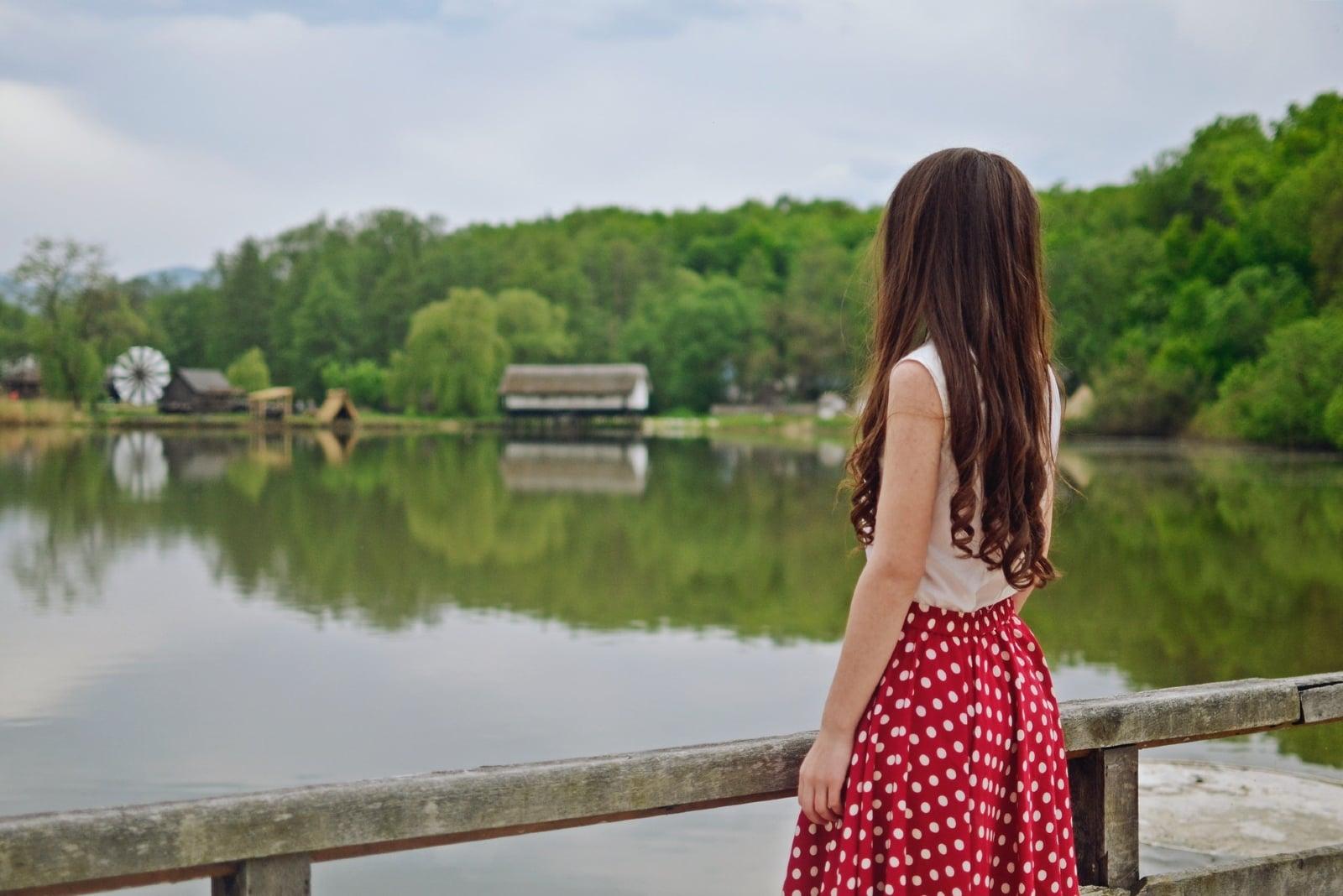 woman standing on bridge looking at water
