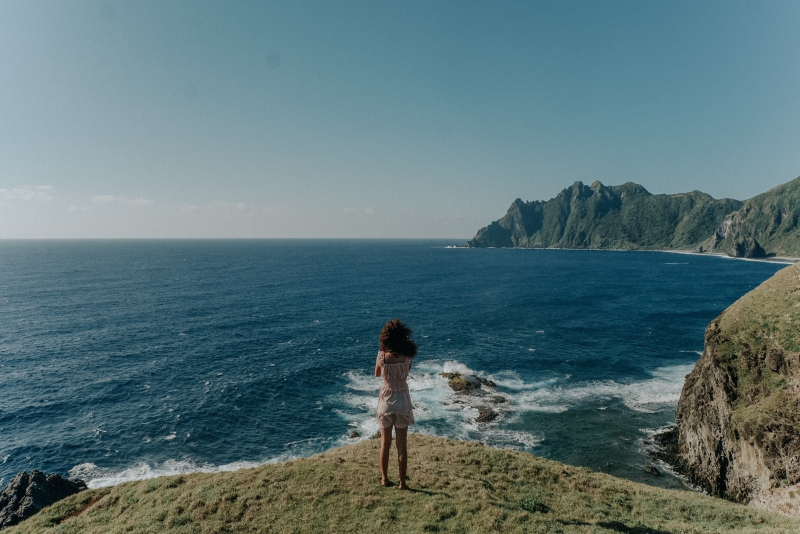 woman looking at sea while standing on cliff
