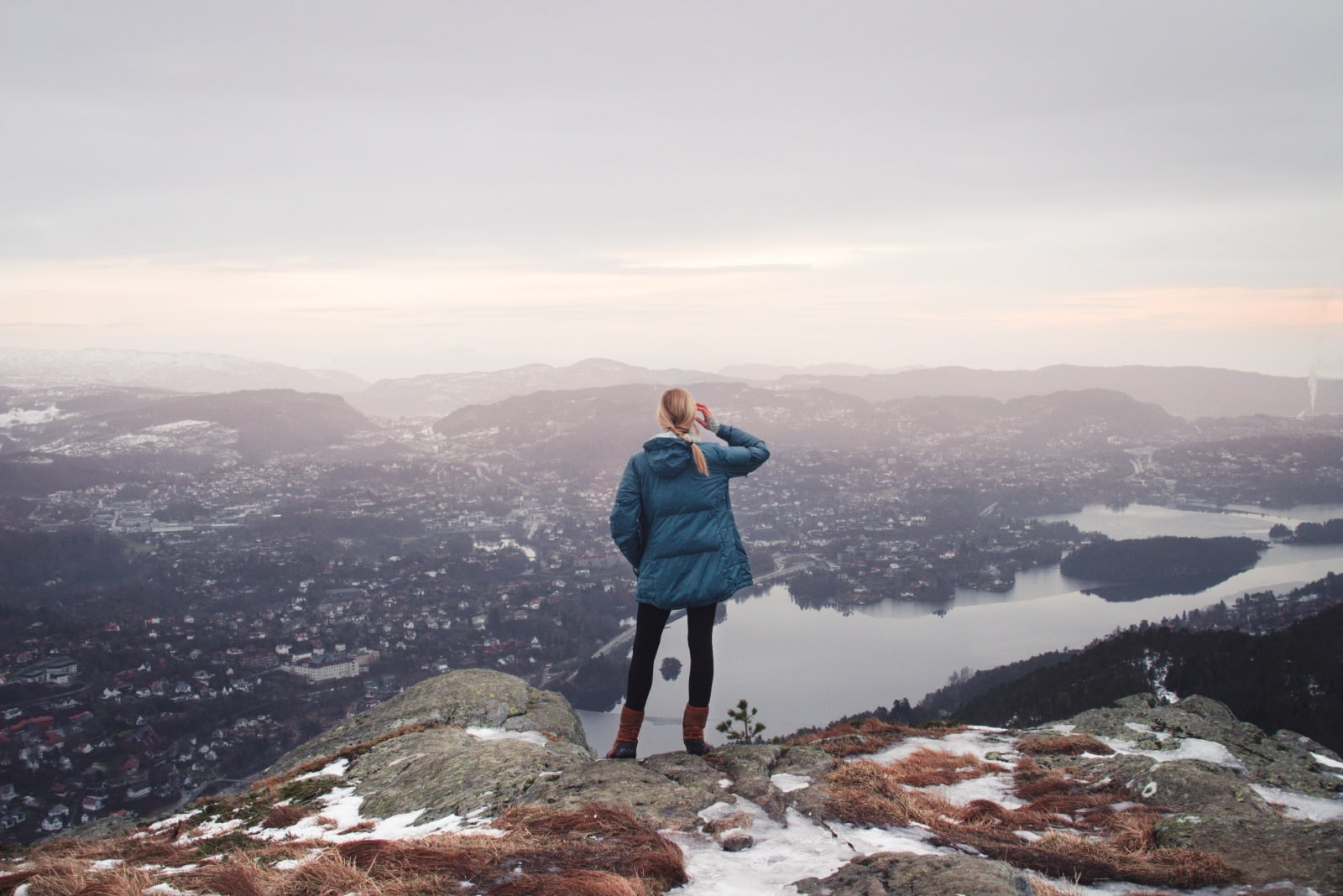 woman in blue jacket standing on cliff looking at lake