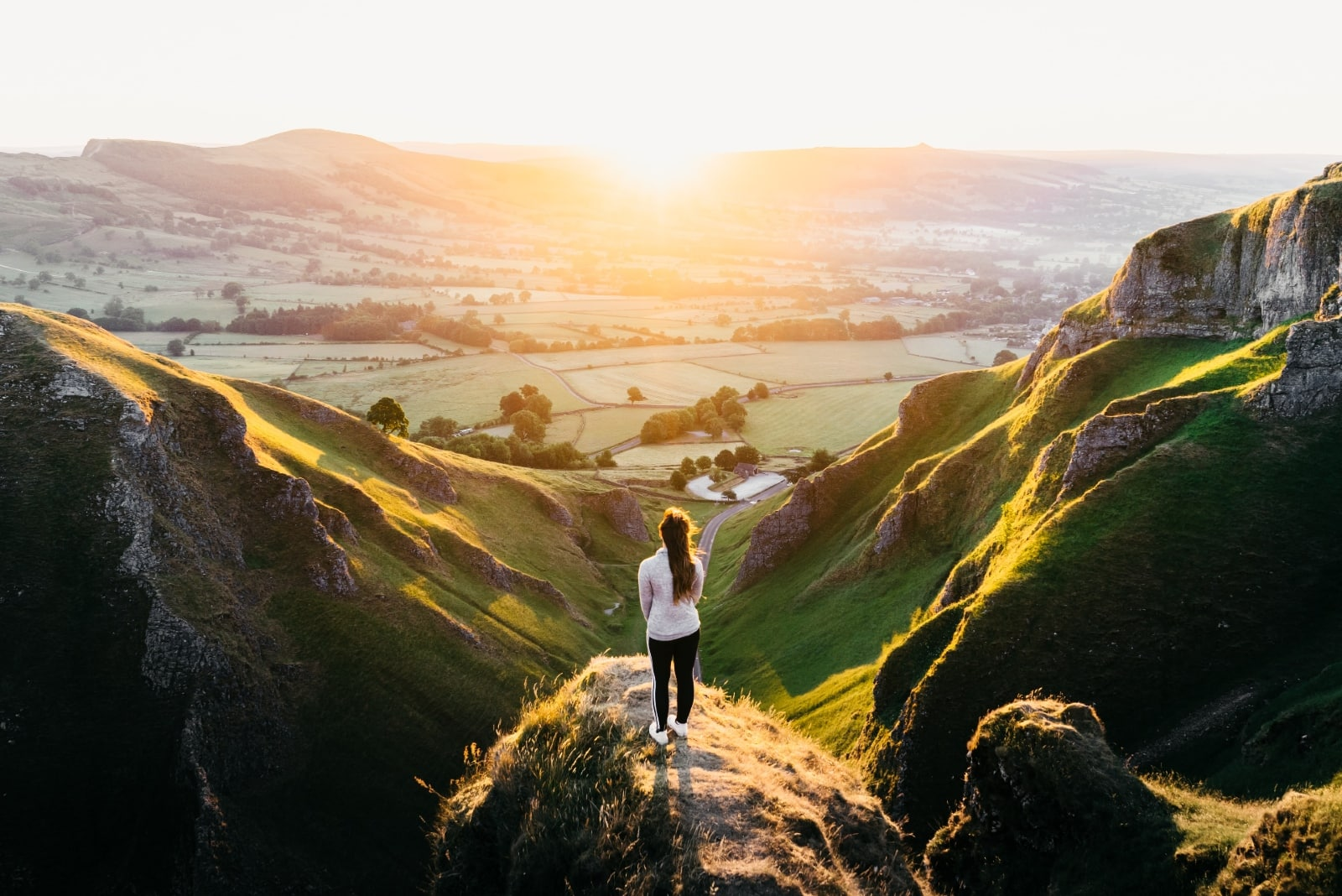 woman standing on hill during sunset